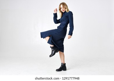 woman in dress raised her leg on a light background