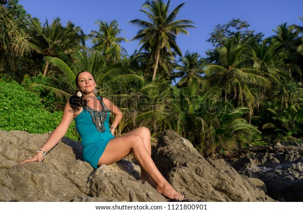 a woman in a dress resting sitting on the stones in the background of the rainforest