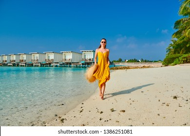 Woman in dress running on tropical beach. Summer vacation at Maldives.