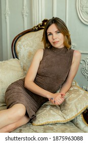 A woman in a dress sits relaxed in a chair in the room. Looks into the camera.