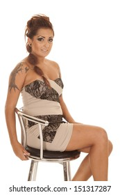 A woman in a dress sitting on a stool has tattoos.