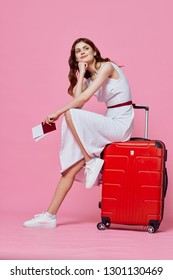 A woman in a dress and sneakers with a passport with documents in her hands is sitting on a red suitcase and is dreamily looking away