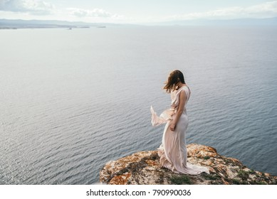 woman in dress standing on the edge of the abyss near the ocean