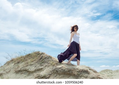 Woman in a dress is standing on a sand hill