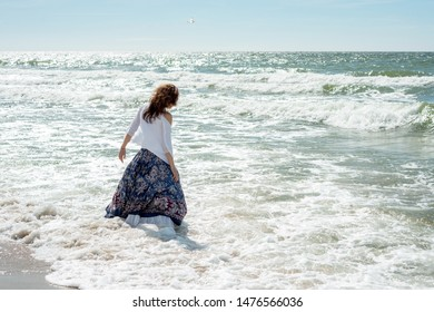 Woman in a dress stands in the water