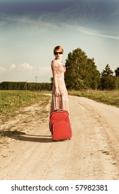 woman in   dress with  suitcase on road