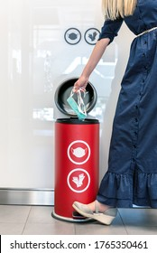 Woman in dress throws used mask in a special waste bin for disposal of specific medical waste