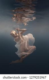 Woman in dress under water