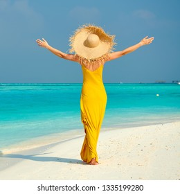 Woman in dress walking on tropical beach with arms outstretched. Summer vacation at Maldives.
