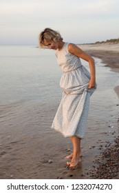 Woman in dress walks barefoot in the water by the sea