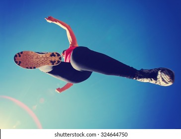 a woman dressed in active wear jumping directly over the camera with a wide angle lens during summer time with a lens flare in the corner