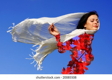 woman dressed in a autumn leaves with a scarf blowing in the wind