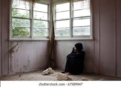 Woman  dressed in black sitting alone in an abandoned home