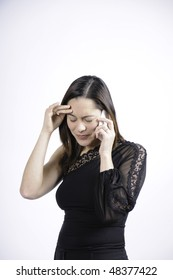 Woman dressed in black talking on the telephone and seems very sad and holding her head. She is of mixed ethnicity.