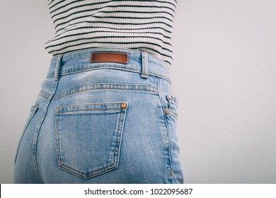 Woman dressed black and white striped sweater and blue jeans. Side view. Copy space