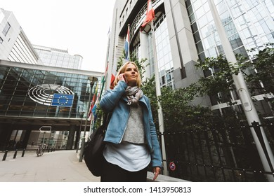 A woman dressed in casual style is walking against the background of the European Parliament building and talking on the phone. The emblem of the European Union. Brussels, Belgium