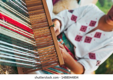 Woman dressed in colorful traditional native Serbian closing knitting a carpet with national pattern