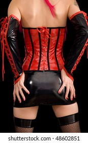 Woman dressed in dominatrix clothes, from back, isolated on black background