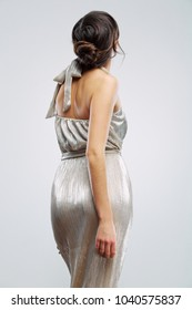 Woman dressed evening silver dress standing back. Isolated studio portrait in fashion style.