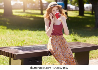 Woman dressed floor skirt, t shirt and hat, charging smart phone via USB outdoors. Public charging on bench with solar panel on street. Alternative electricity source and modern technology concept.