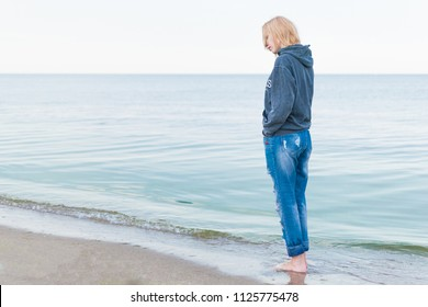 A woman dressed in jeans and a sweater stands on the seashore in the water. Concept Women's loneliness, depression.