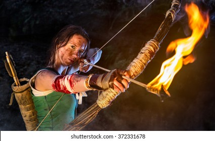 Woman dressed up as Lara Croft aiming with a bow and pulls the bowstring with a burning arrow.