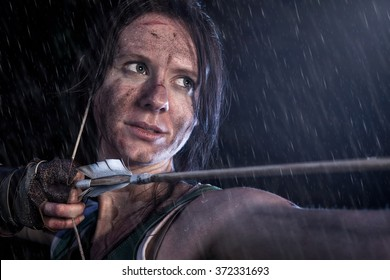 Woman dressed up as Lara Croft stands in the rain, aiming with a bow and pulling the bowstring with a arrow.