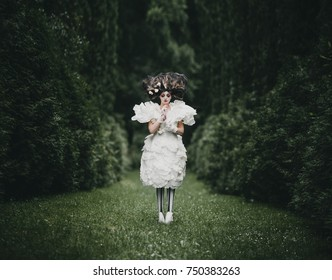 Woman dressed like a hero from 'Alice in Wonderland' poses in a green park