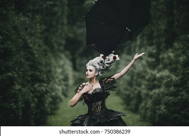 Woman dressed like a hero from 'Alice in Wonderland' poses with black umbrella in a green park