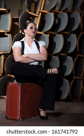 Woman dressed as a man sits on stage at the old suitcase