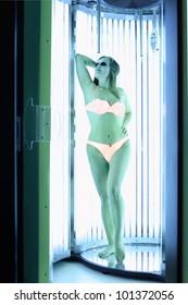 Woman dressed in orange swimsuit and dark glasses stands in solarium; full body