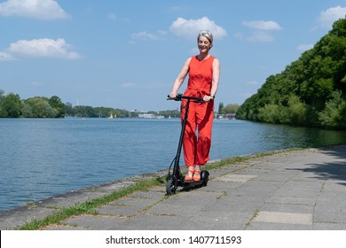 Woman dressed in red drives e-scooter at a lake
