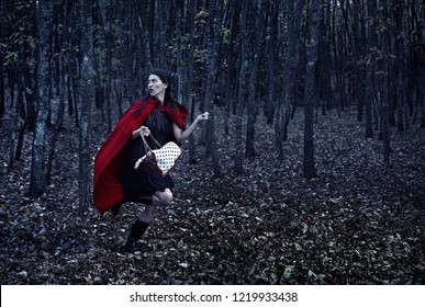Woman dressed as Red Riding Hood running at night through the forest