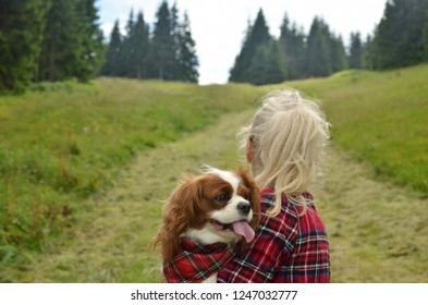 Woman dressed in royal stewart hiking with her dog - Cavalier King Charles Spaniel - having a collar with a same pattern hiking on mountain path