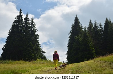 Woman dressed in royal stewart hiking with her dog - Cavalier King Charles Spaniel - on mountain path