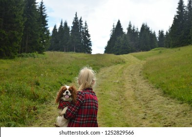 Woman dressed in royal stewart hiking with her dog - Cavalier King Charles Spaniel - having a collar with a same pattern on mountain path