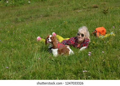 Woman dressed in rustic royal stewart shirt, lying on green meadow resting with her pet - Cavalier King Charles Spaniel