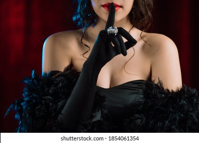 Woman dressed in style of Roaring twenties last century demonstrates shhh silence sign gesture. Flappers, retro fashion, vintage lady costume