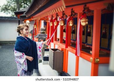 Woman dressed in traditional japanese costume (Kimono) walking under tori gates at the Fushimi-inari shrine, Kyoto Japan