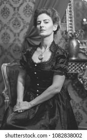 Woman dressed with a victorian black dress sitting and posing (black/white and noisy vintage image)