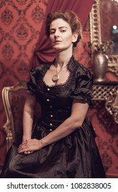 Woman dressed with a victorian black dress sitting and posing.