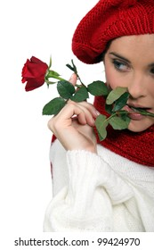 Woman dressed for winter holding rose