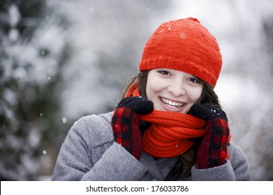 A woman dressed for winter pulls her scarf down and smiles.