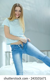 Woman dressed. Young blond hair woman lying on the bed and pulling on skinny jeans