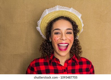 Woman dressing checked pattern clothes on jute fabric backdrop. Brazilian girl wearing red plaid shirt laughing at camera. Make up for Festa Junina: party in Brazil in the month of june.