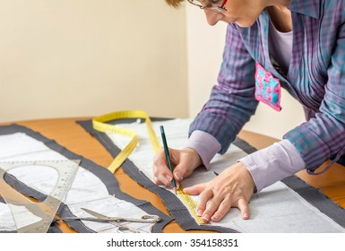 Woman dressmaker drawing tailor pattern with pencil for a suit on the table