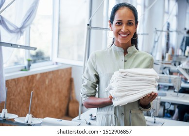 Woman dressmaker stands in the factory with cloth in hands.