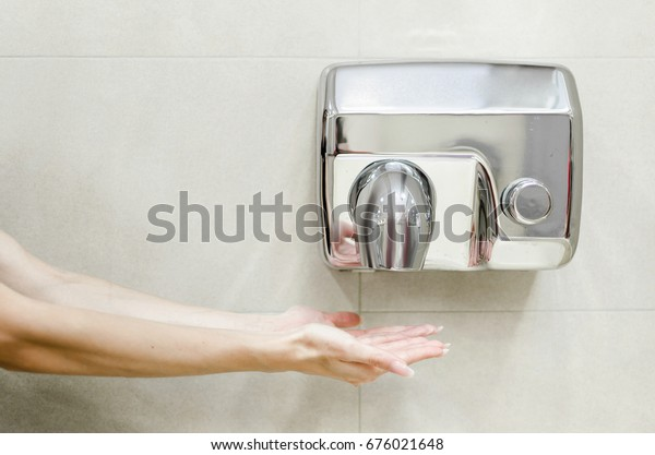 Woman dries her hands in the bathroom