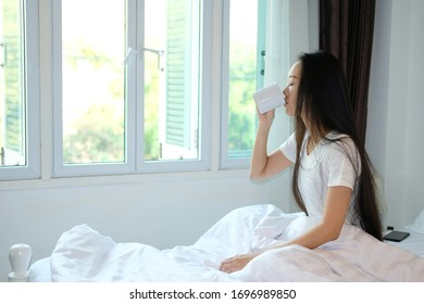 woman drink a cup of coffee in bedroom