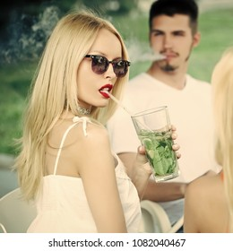 woman drink mojito cocktail with man. Man vaping hookah pipe with girlfriend in bar. Friends at shisha cafe lounge. Love, cheating, date, relationship. Bad habits, party, addiction.